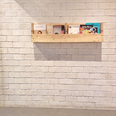 White, brick walls and a simple rack of reading of materials that adorn it. So simple and classy.